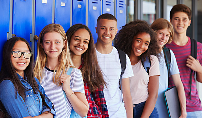 Diverse group of teens standing in front of lockers at school.