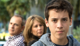 Adolescent male teen with parents in background