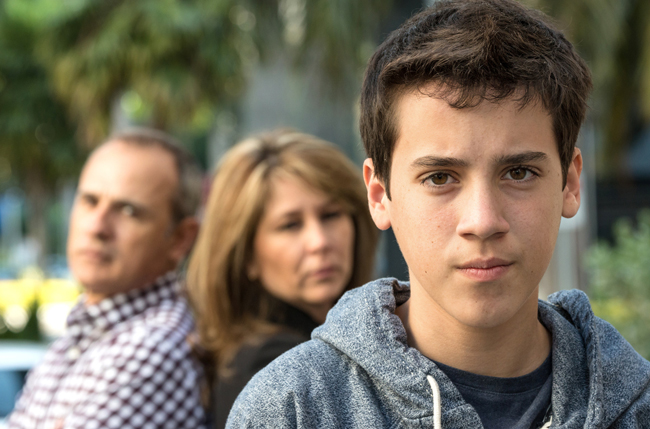 A picture of a teenage boy with his parents in the background.