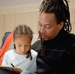 African American dad helping his daughter with homework
