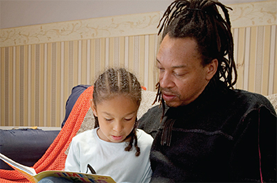 Father sitting with child writing