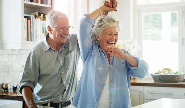 Older couple laughing and dancing in the kitchen.