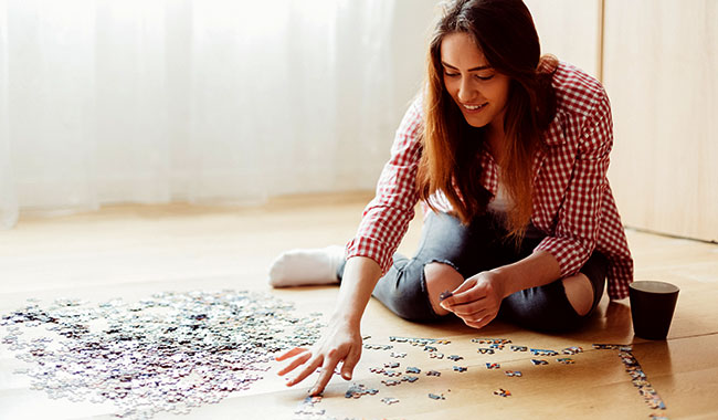 Smiling woman working a puzzle on the floor.