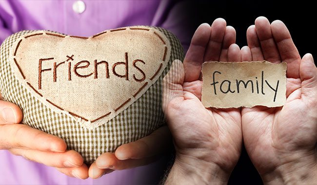 Hands cradling am embroidered pillow that says friends beside hands cupping a paper that says family.