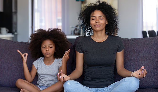 Mindful African American mom with daughter having fun doing a yoga pose.