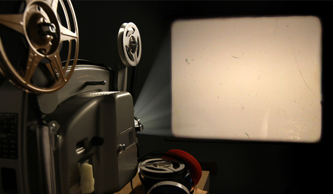 film projector projecting on a blank screen