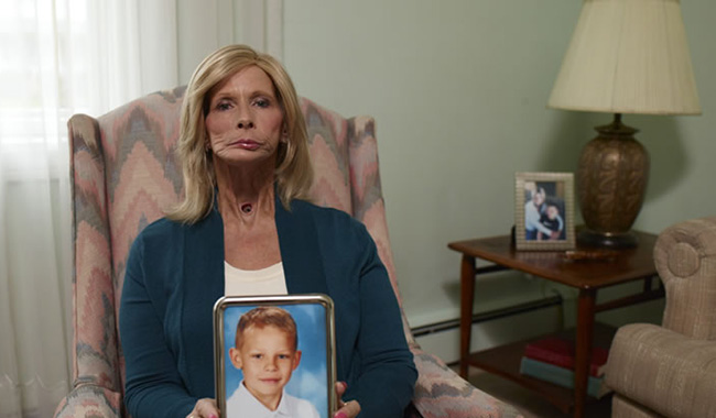 Terrie holding a photo of her grandson