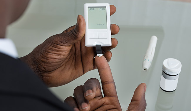 Man checking his blood glucose level with a meter.