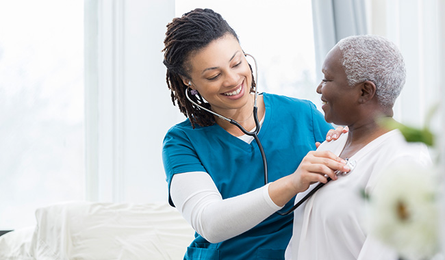 Nurse practitioner listening to patient's heart with stethoscope,