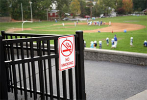 Photo of a practice field with a no smoking sign