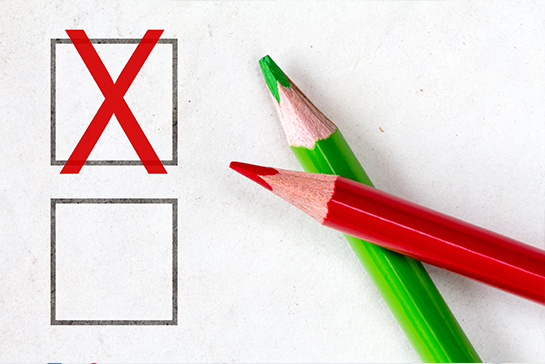 Colored pencils beside a checkbox with a red X