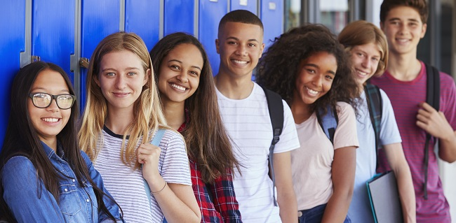 Teenage school kids smiling to camera in school corridor