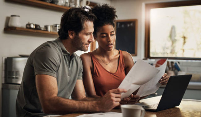 Man and woman reviewing paperwork in front of laptop