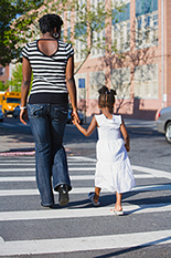 Mother and daughter crossing street in crosswalk