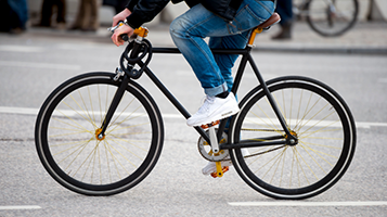 Photo of a biker wearing jeans riding a bicycle.