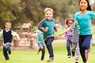 Photo of six children outside running towards the camera.