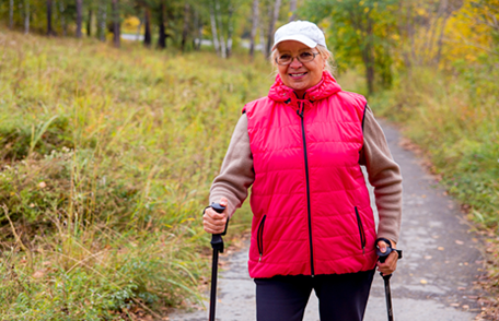 an older woman in a pink jacket hiking with the aid of hiking sticks