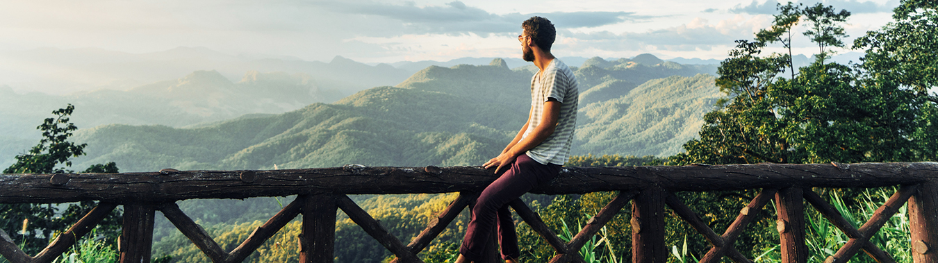 Man sitting on a wooden fence with mountains in the background