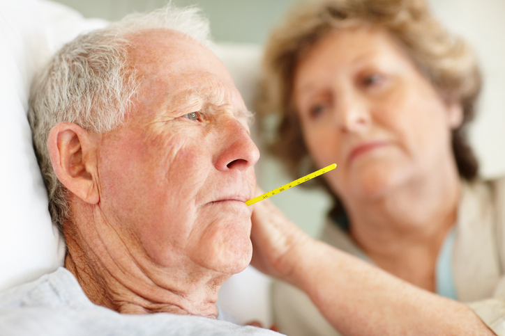 Elderly sick man in bed with a thermometer in his mouth.