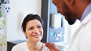 Male doctor talking with female, smiling patient