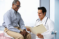Male patient sitting next to a male doctor with medical chart