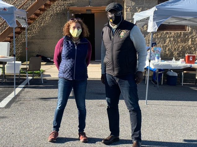 man and woman in masks at a community event