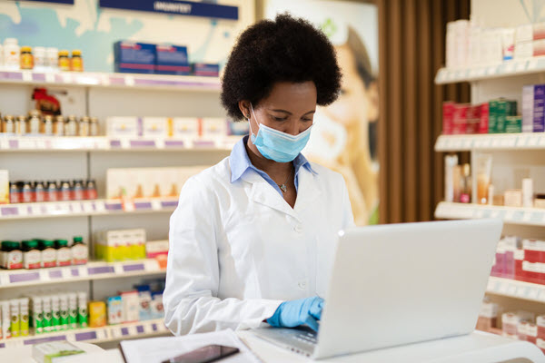 Pharmacist in a mask, typing on a laptop.