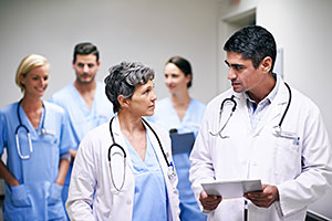 Doctors discussing a chart in a hallway with nurses following behind
