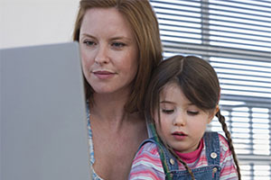Mother sitting with daughter while on the laptop.