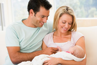 Couple in living room with baby.