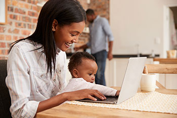 African-American mom looks up vaccine information on a laptop while holding her baby.