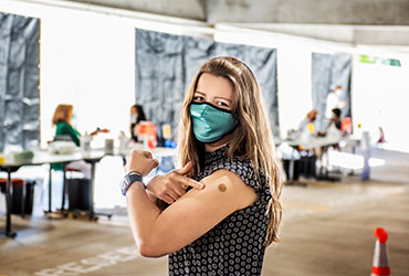 Woman in a mask pointing to her arm where she was vaccinated.