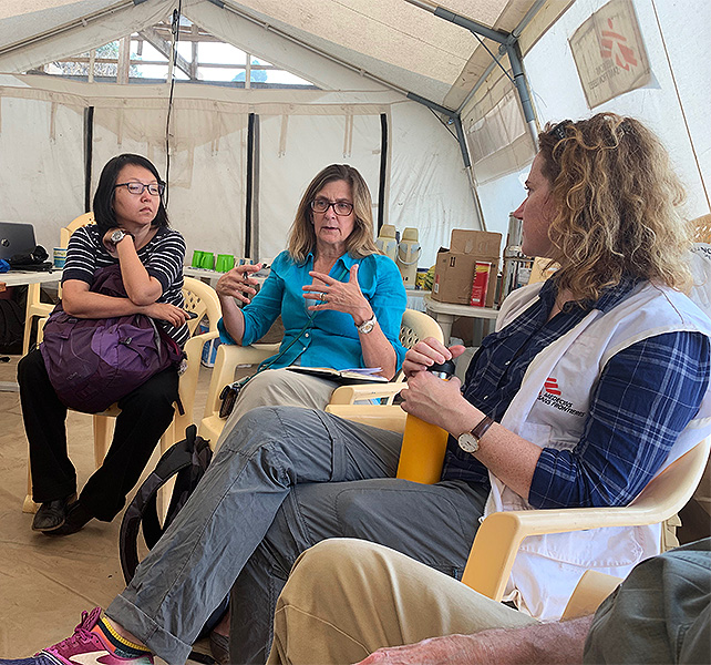 a group of Ebola responders holding a meeting in a tent