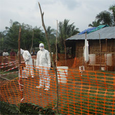 MSF (Medicins Sans Frontiers) health staff in protective clothing constructing perimeter for isolation ward.