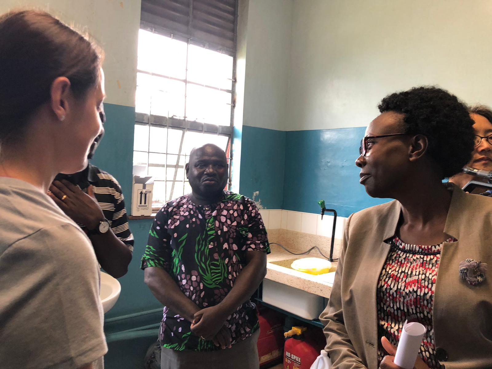 Amy Schuh, Luke Nyakarahuka, and Jackson Kyondo show the Ugandan Minister of Health the Ebola field laboratory in Bwera, Uganda