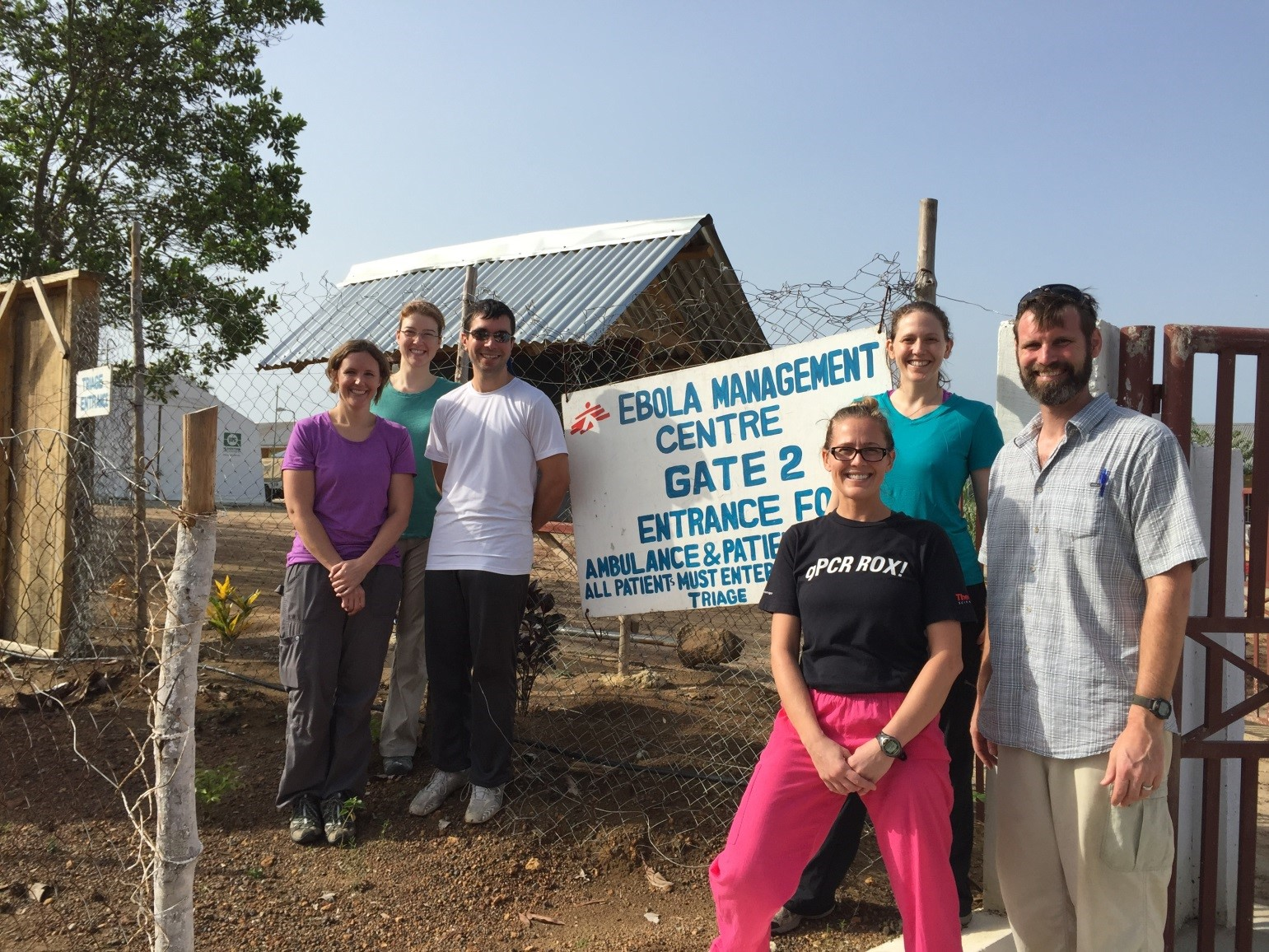 Members of the Bo lab (Team 12) standing in front of the entrance to the Médecins Sans Frontières compound, where the lab is located. (Left to right) Janae Stovall, Laura Rose, Marko Zivcec, Lauren Andersen, Shannon Emery, and Brian Bird