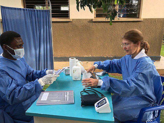 CDC's Rosalind Carter and a Ugandan colleague prepare to give the Ebola vaccine to health workers