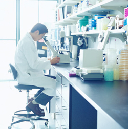 man in a laboratory looking into a microscope