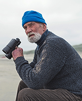 Older gentlemen on beach with binoculars