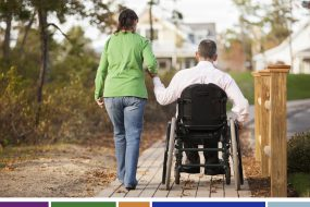 woman holding husband's hand who is in a wheelchair