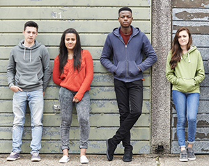 Teens standing against wall