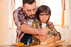 father and child wearing eye protection while woodworking