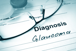 eyeglasses lying on paper with glaucoma diagnosis written