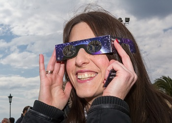 woman looking up with solar eclipse glasses