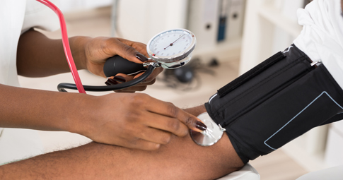 Nurse checking blood pressure on African american woman