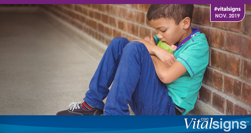 A child hugging a toy to his chest while sulking against a brick wall.