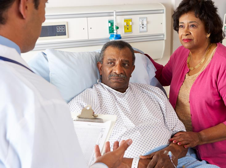 A physician talks with a patient who is sitting in a hospital bed