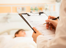 Health care professional writing on clip board and patient laying down on the background
