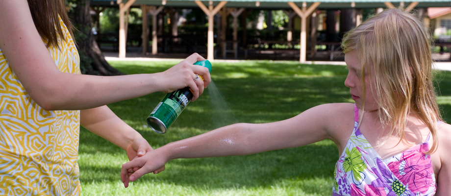 Spraying insect repellent over girl's arm