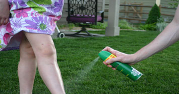 bug repellant being sprayed onto a girls legs